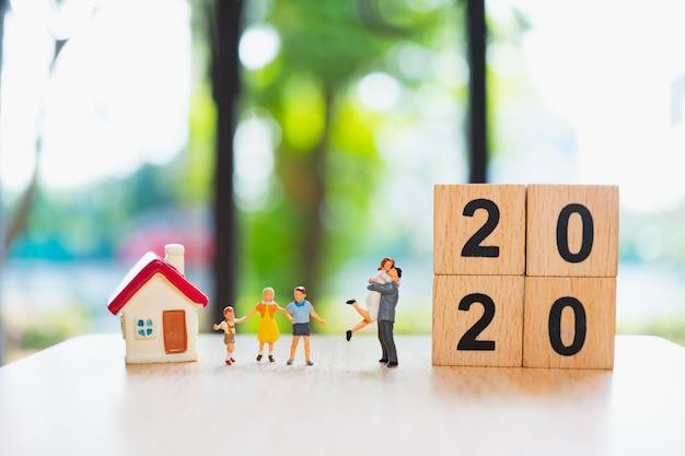 Famiglia in miniatura in piedi con mini casa e blocchi di legno 2020