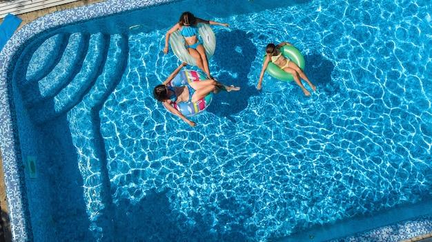 Famiglia in piscina vista aerea del drone dall'alto, madre e bambini felici nuotano su ciambelle gonfiabili e si divertono in acqua in vacanza con la famiglia, vacanze tropicali in resort