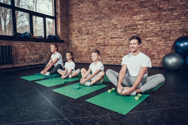 Famiglia in pratica sportiva yoga e regge il pollice in alto