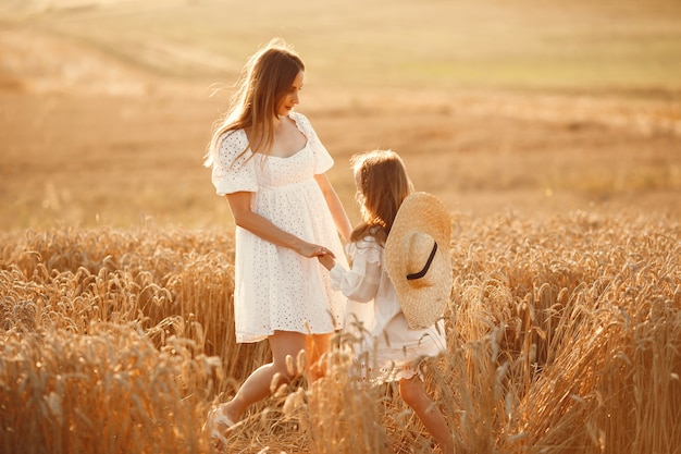 Famiglia in un campo di grano. donna in abito bianco. ragazza con cappello di paglia.