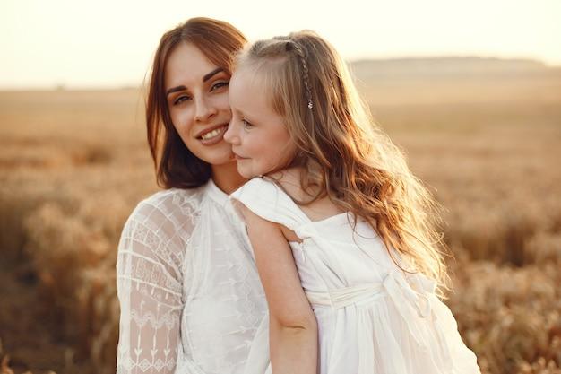 Famiglia in un campo estivo. foto sensuale. piccola ragazza carina. donna in abito bianco.