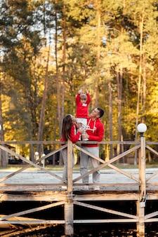 Famiglia in una passeggiata nel parco in autunno vicino allo stagno. padre e mamma che tengono le mani della figlia.