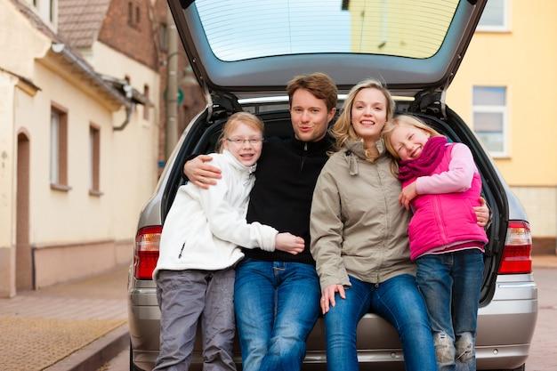 Famiglia in viaggio in auto seduto nella parte posteriore