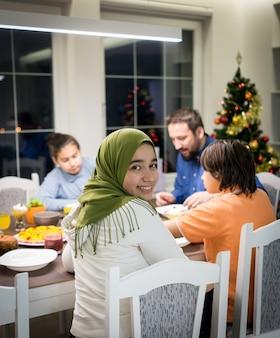 Famiglia interreligiosa musulmana con albero di natale