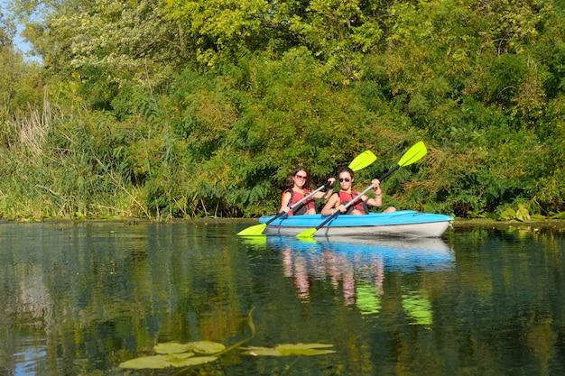 Famiglia kayak, madre e figlia pagaiando in kayak sul tour in canoa sul fiume divertendosi, weekend autunnale attivo e vacanze con bambini, concetto di fitness