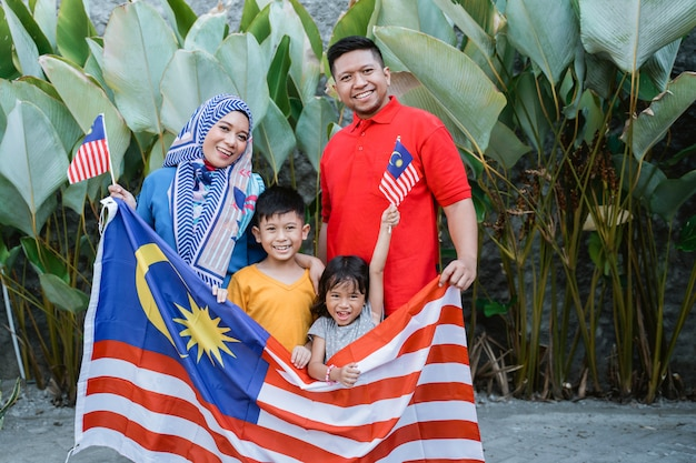 Famiglia malese che tiene la bandiera della malesia davanti alla loro casa