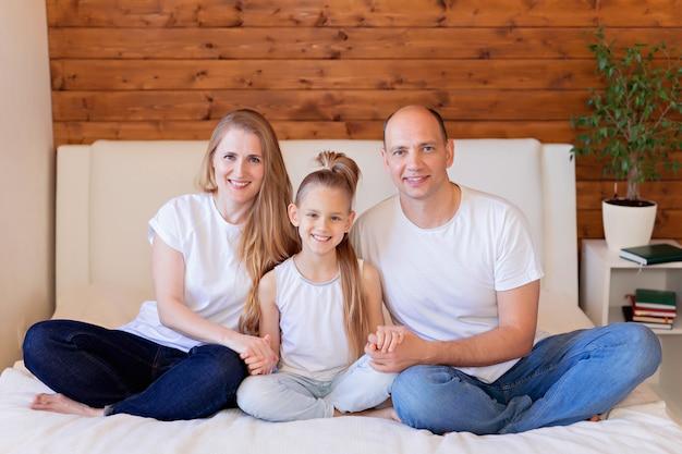 Famiglia, mamma, papà e figlia felici a letto a casa nella camera da letto