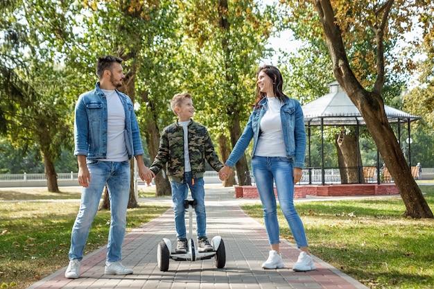Famiglia moderna, papà mamma figlio cavalca un hoverboard nel parco
