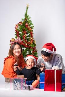 Famiglia molto felice con un regalo al giorno di natale e felice anno nuovo sullo sfondo in studio