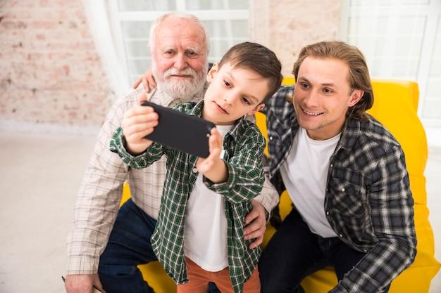 Famiglia multi-generazionale sorridente che prende selfie con lo smartphone