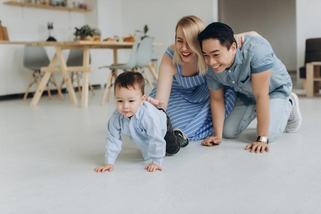Famiglia multiculturale felice divertirsi insieme in cucina. papà asiatico e mamma caucasica insegnano al figlio a gattonare