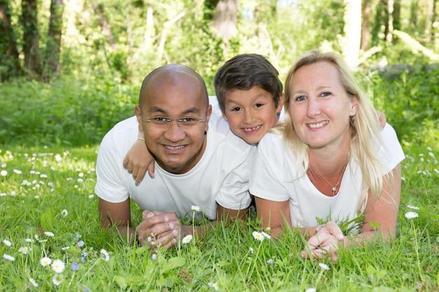 Famiglia multietnica felice che lyong su erba con i bambini. coppie sorridenti con look sonico alla macchina fotografica. la madre e il padre nero sul giardino parcheggiano all'aperto