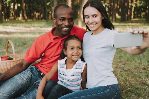Famiglia multinazionale che fa un selfie sul picnic.