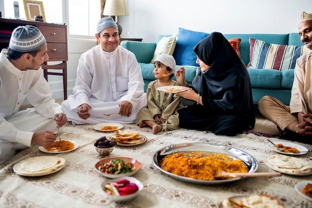 Famiglia musulmana cenando sul pavimento