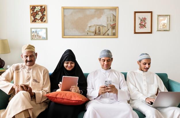 Famiglia musulmana utilizzando dispositivi digitali a casa