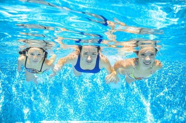 Famiglia nuota in piscina sott'acqua, felice madre attiva e bambini si divertono sott'acqua, fitness e sport con i bambini in vacanza estiva in resort