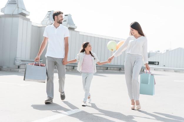 Famiglia, padre, madre e figlia con borse della spesa.