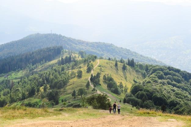 Famiglia padre, madre e figlio viaggiano in montagna