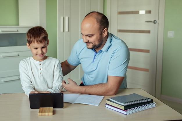 Famiglia papà e figlio sono seduti in una stanza a casa al tavolo e fanno i compiti usando un tablet.