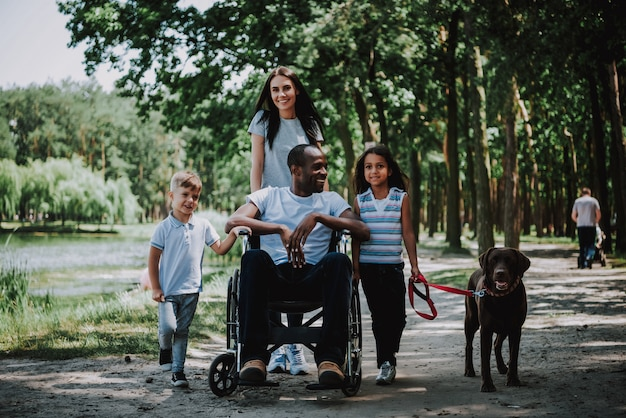 Famiglia positiva nell'uomo del parco nel sorridere della sedia a rotelle.