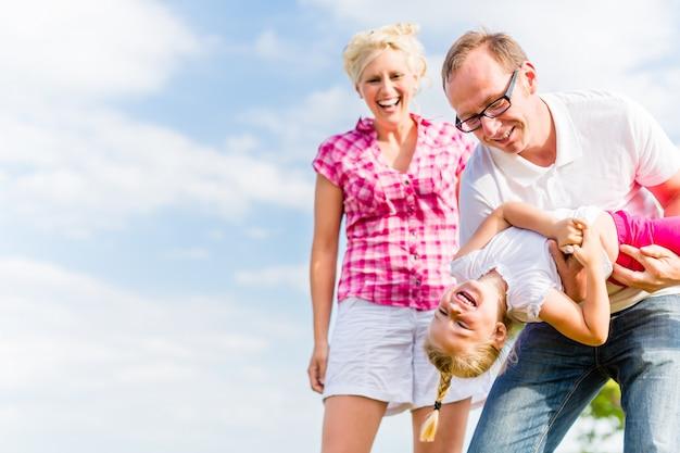 Famiglia scatenarsi sul campo con i genitori che trasportano bambino