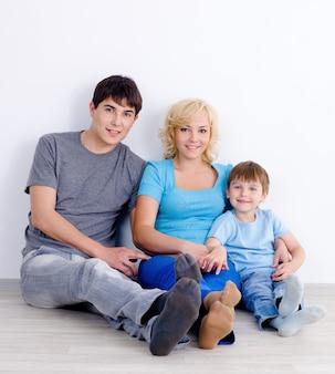 Famiglia seduti insieme sul pavimento