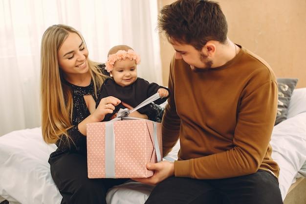 Famiglia seduto a casa su un letto con regali