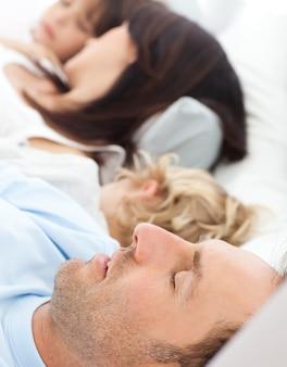 Famiglia serena che dorme insieme al mattino