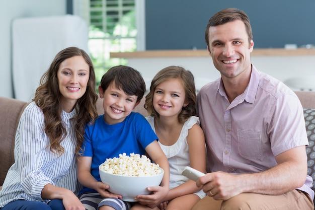 Famiglia sorridente che guarda tv e che mangia popcorn in salone a casa