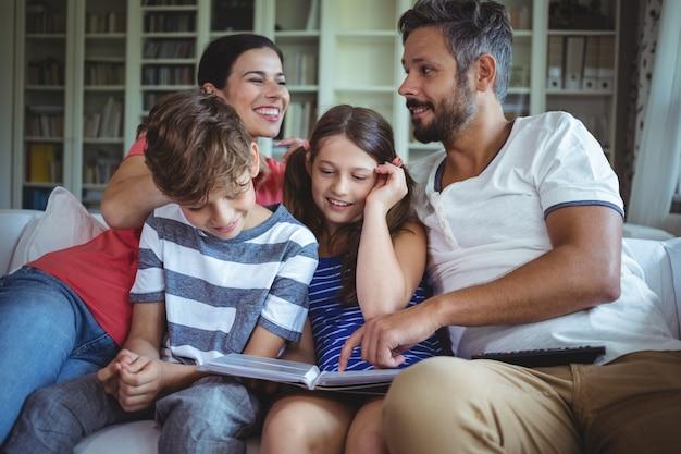 Famiglia sorridente che si siede sul sofà e che esamina un album di foto
