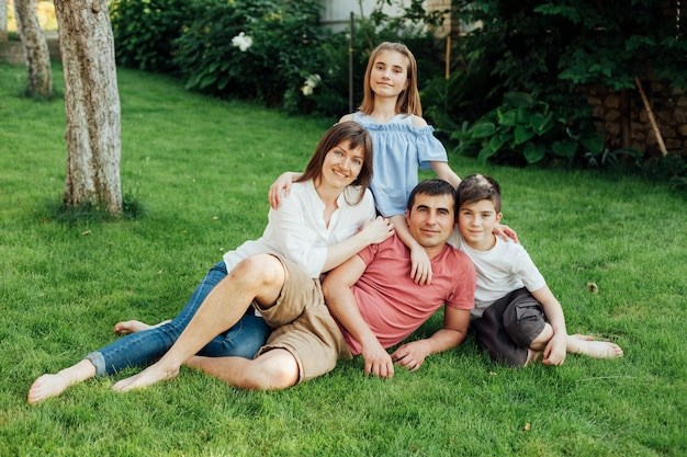 Famiglia sorridente che si siede sull'erba a all'aperto