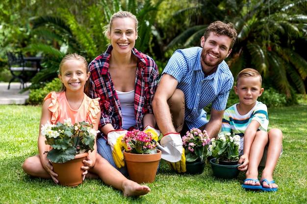 Famiglia sorridente con i vasi di fiori su erba all'iarda