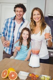 Famiglia sorridente con succo di frutta