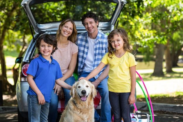 Famiglia sorridente davanti a un'auto