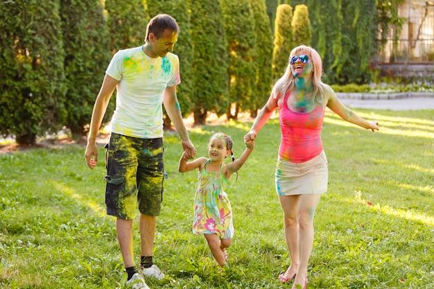 Famiglia sorridente felice in vernice holi