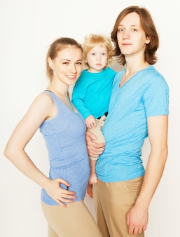 Famiglia sportiva felice - madre, padre e figlio piccolo che posano sopra lo spazio bianco