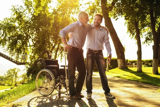 Famiglia su sunny road. figlio aiuta nonno a stare in piedi.