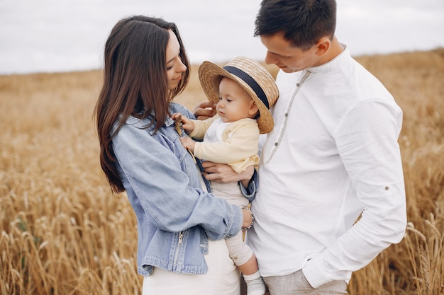 Famiglia sveglia che gioca in un campo di autunno