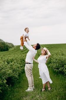 Famiglia sveglia che gioca in un campo estivo