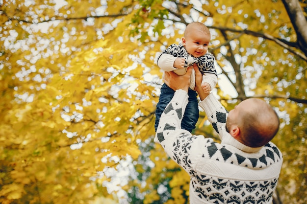 Famiglia sveglia che gioca in un parco di autunno