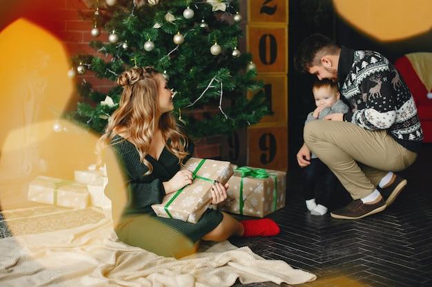 Famiglia sveglia che si siede vicino all'albero di natale