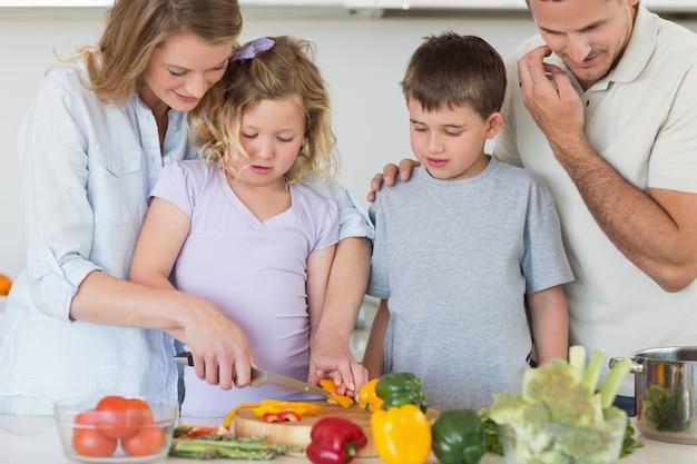 Famiglia tagliare le verdure in cucina