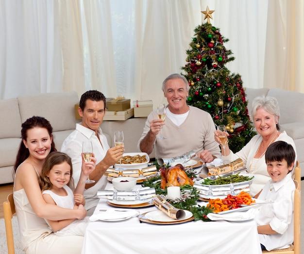 Famiglia tusting con vino bianco in una cena di natale