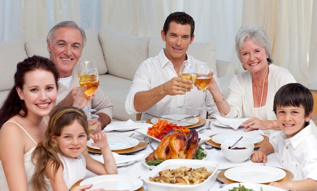 Famiglia tusting con vino in una cena sorridendo alla telecamera