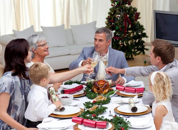 Famiglia tusting in una cena di natale con champagne