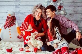 Famiglia vestita fantasia pone prima albero di Natale bianco