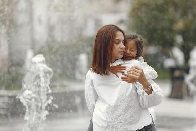 Famiglia vicino alla fontana della città. madre con la figlia che gioca con l'acqua.