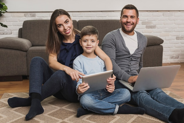 Famiglia vista frontale con laptop e tablet