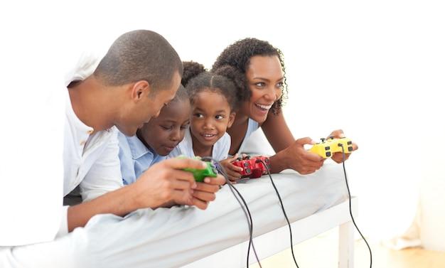 Famiglia vivace che gioca video gioco sdraiato sul letto