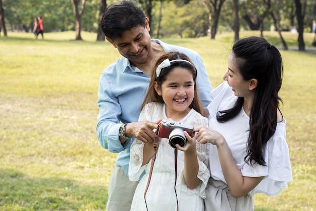Famiglie asiatiche che guardano le foto dalle loro macchine fotografiche.